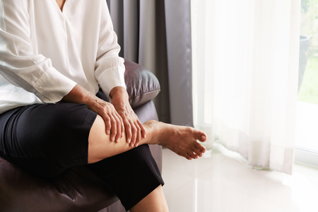 leg cramp, senior woman suffering from leg cramp pain at home, health problem concept