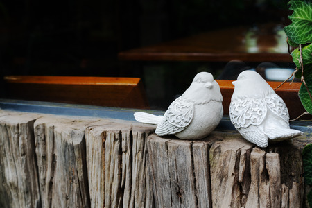 Couple birds, two white bird statues on the wooden near window Фото со стока