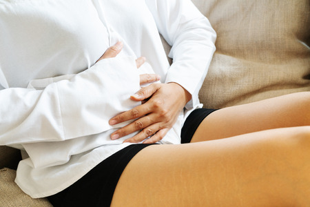 Young woman suffering from abdominal pain while sitting on the sofa and feeling stomachache, symptom of pms