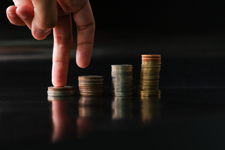 fingers step upward on stack of coins on black background concept business finance growing