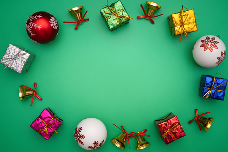 Christmas composition. Christmas gift, bell and ball on green background. Flat lay, top view, copy space