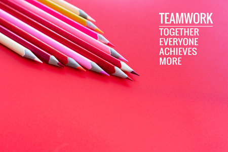 Teamwork concept. group of color pencil on pink background with word Teamwork, Together, Everyone, Achieves and More