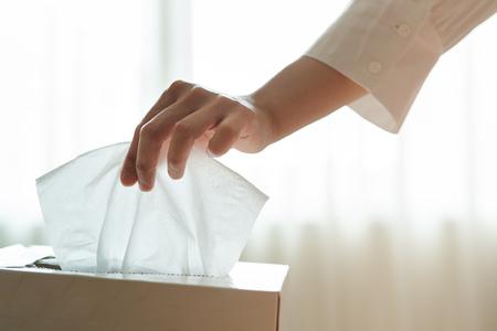 Les femmes cueillent à la main une serviette / papier de soie dans la boîte de mouchoirs Banque d'images
