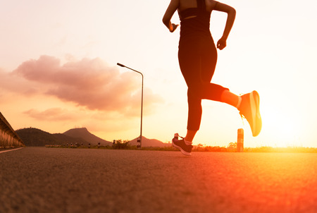 sport woman running on a road. Fitness woman training at sunset