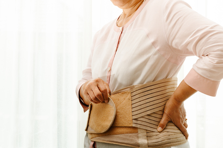 back pain, senior woman wearing back support belt on white background Stockfoto