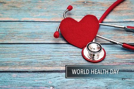 World health day, healthcare and medical concept, red stethoscope and red heart on the blue wooden background