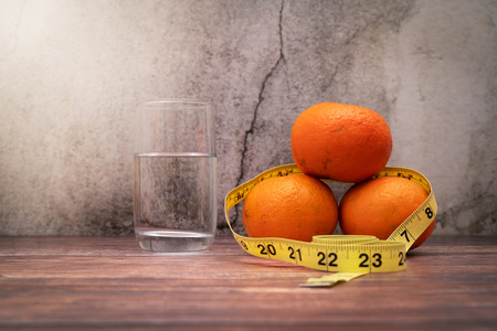 Fresh fruit for diet, measuring tape and drinking water on wooden table. Concept of diet and healthy lifestyle