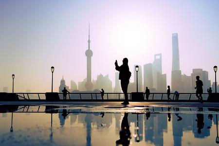 traveler take a photo of morning activity at the bund, huangpu riverside, shanghai city view background