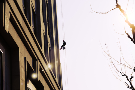 worker cleaning outdoor windows service on high rise building