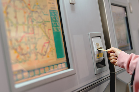 Woman hand inserts card to buy subway train ticket in machine. Transportation concept