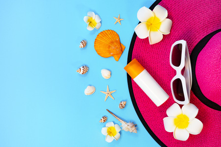 Beautiful summer holiday, Beach accessories, sunglasses, hat, sunblock and shells on blue background