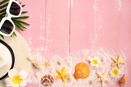 Beautiful summer holiday, Beach accessories, seashells, sand, hat, sunglasses and palm leave on wooden backgrounds