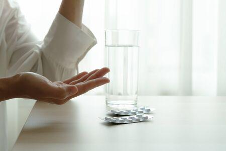 les femmes déprimées tiennent un médicament avec un verre d'eau, des soins de santé et un concept de récupération de médicaments
