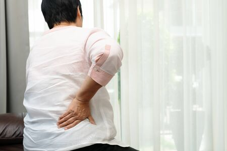 Old woman back pain at home, health problem concept Stock Photo
