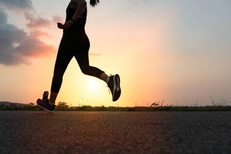 mujer deportiva corriendo en una carretera. Entrenamiento de mujer fitness al atardecer Foto de archivo