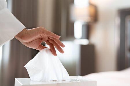 women hand picking napkin/tissue paper from the tissue box