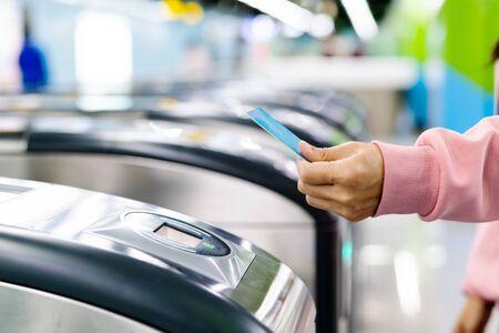 Main de femme scannant un billet de train jusqu'à la porte d'entrée du métro. Notion de transport