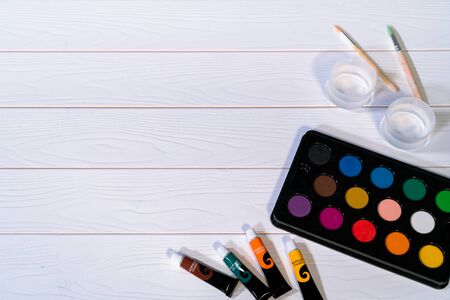 palate of water color paint on the white wooden table