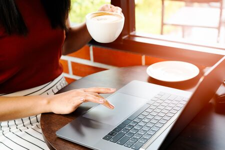 Asia woman hold cup of coffee while typing on laptop keyboard. Woman working at office with coffee