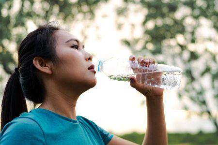 Fitness Asia mujer agua potable después de correr Foto de archivo