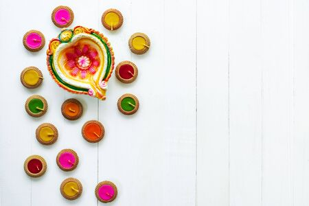 Happy Diwali - Clay Diya lamps lit during Dipavali, Hindu festival of lights celebration. Colorful traditional oil lamp diya on white wooden background Фото со стока
