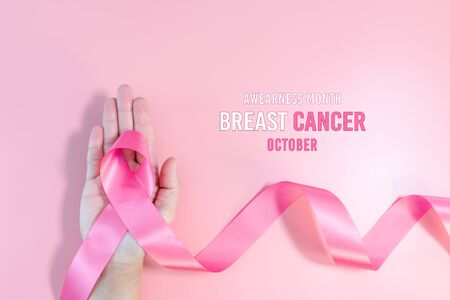 Pink ribbon symbol. Breast Cancer Awareness Month Campaign. Woman hand hold the pink ribbon on pink background Banque d'images