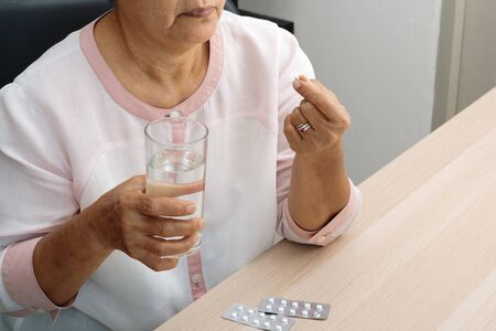 headache old women hand hold medicine with a glass of water, feeling stress, migraine, health problem concept