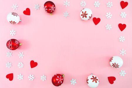 Composición navideña. Bolas de Navidad, corazón rojo y adornos de copos de nieve sobre fondo rosa. Endecha plana, vista superior, espacio de copia