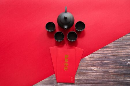 Chinese New Year offering red envelope and Chinese tea pot , Translation of text appear in image: Happy New Year