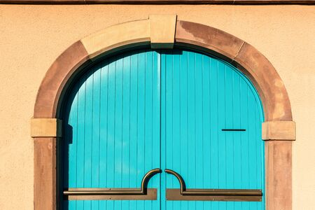 Blue wooden door on brick cement wall background