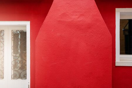 red outdoor wall cement texture with vintage door on abstract background