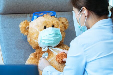 Doctor and patient. Physician examining brown bear wearing mask against virus and flu. Regular medical visit in clinic. Medicine and health care concept Banco de Imagens - 139491669