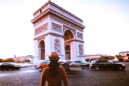 Arc de Triomphe and traveler in Paris street at night twilight