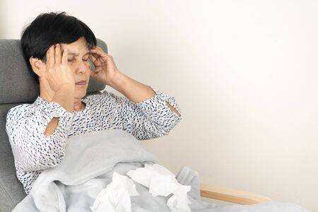 sick senior woman headache with dirty tissue. ill person wearing blanket woolen lay down on sofa