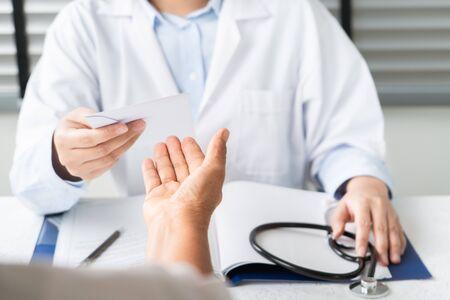 Doctor writing diagnosis and giving a medical prescription to senior women Patient Banco de Imagens