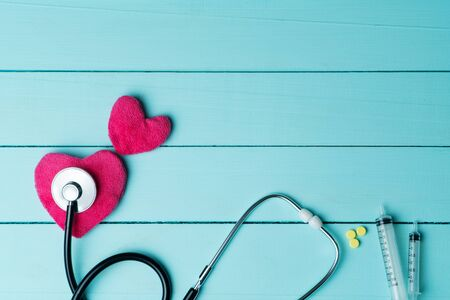 World heart health day concept and Healthcare medical insurance with red heart and stethoscope on blue wooden background