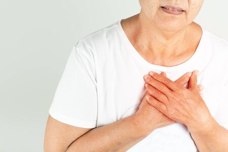 Old woman heart attack holding breast on white background