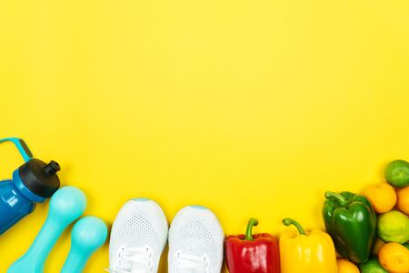 Healthy lifestyle, food and sport concept. athletes equipment and fresh fruit and vegetable on yellow background. Banco de Imagens