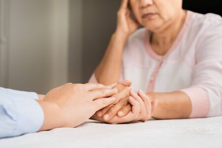 Doctor hands together holding senior woman patient