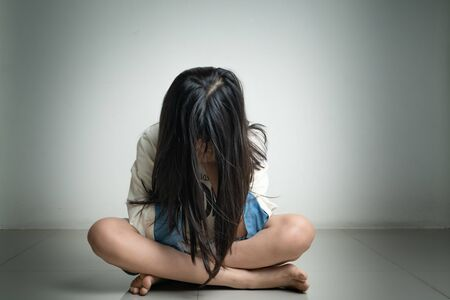 Alone and scared, sad depressed children close her face in the dark room after get bullied