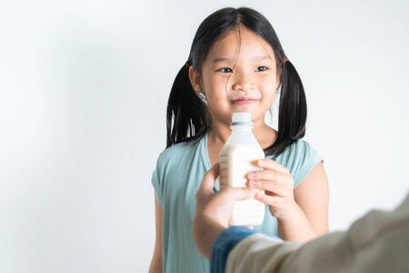woman giving her daughter a bottle of milk at home