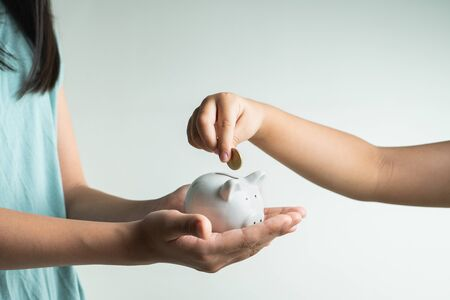 Saving and business concept, two little girl with piggy bank and coins at home