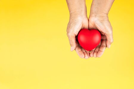 World health day concept Healthcare medical insurance with red heart on senior womans hands support Banco de Imagens