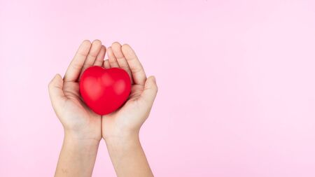 world health day, child hands holding red heart, healthcare, love and family insurance concept Banco de Imagens