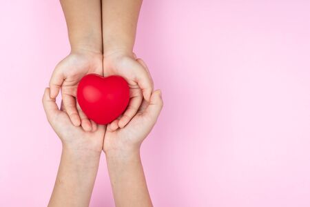 world health day, adult and child hands holding red heart, healthcare, love and family insurance concept