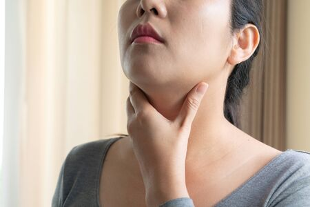 Sore Throat. Beautiful woman hand touching her pain neck. Woman healthcare concept