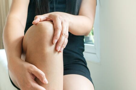 women knee painful, women touch the pain knee at home Banco de Imagens