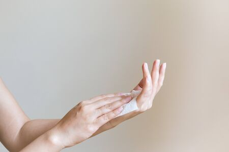 Woman cleaning her hands with white soft tissue paper. isolated on a white backgrounds Banco de Imagens