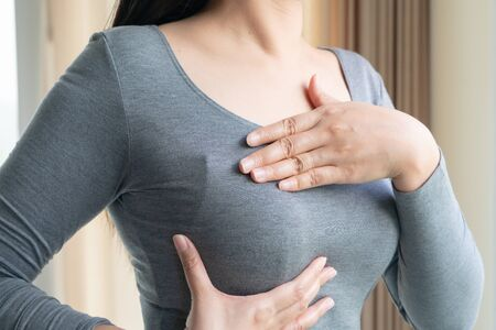 Woman hand checking lumps on her for signs of cancer. Women healthcare concept.