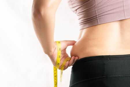 fat woman, fat belly, chubby, obese woman hand pinching on her excessive belly fat waist with measure tape, woman diet lifestyle concept - rear view Banco de Imagens